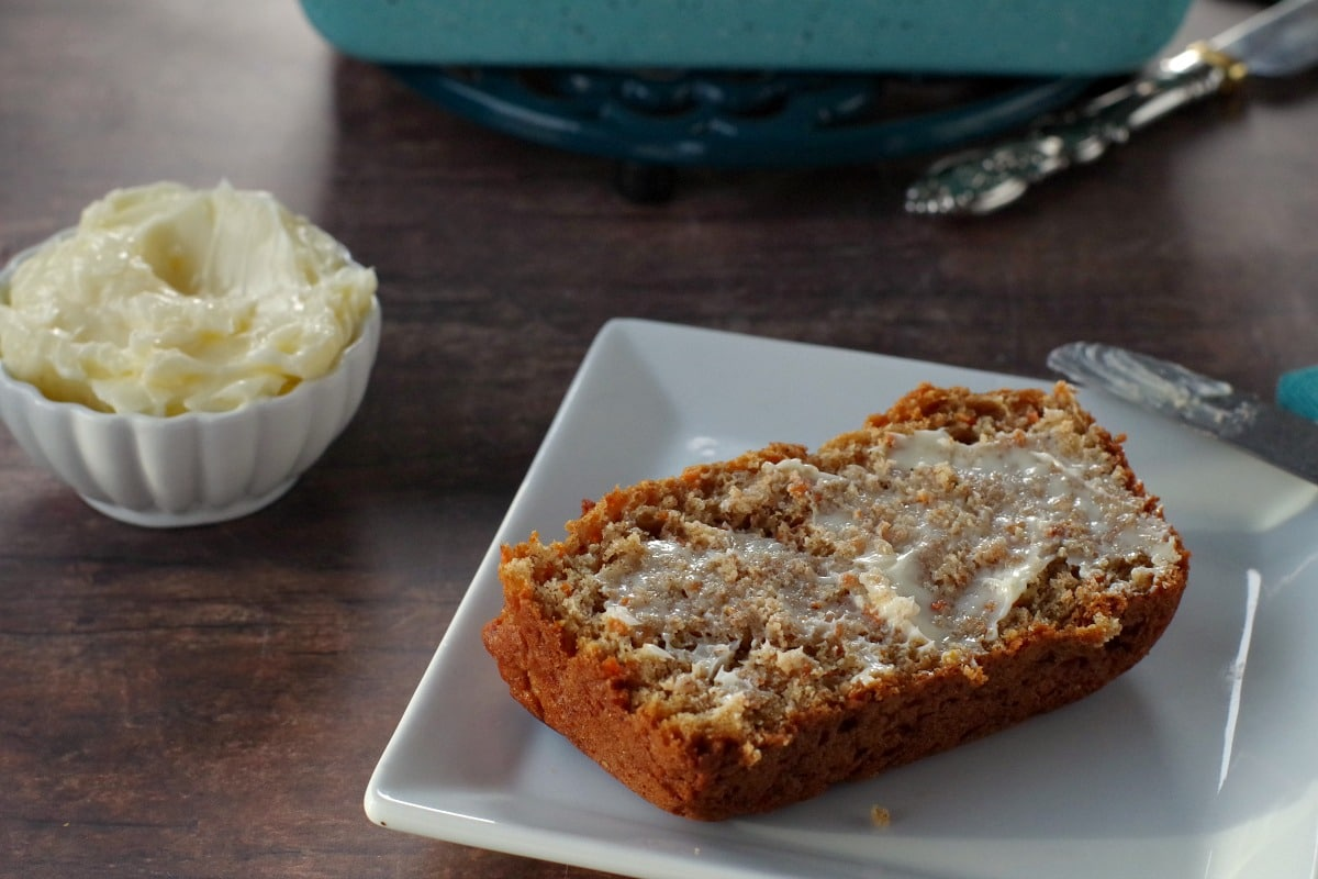 healthy carrot loaf slice with butter on a white plate with white dish of butter in the background