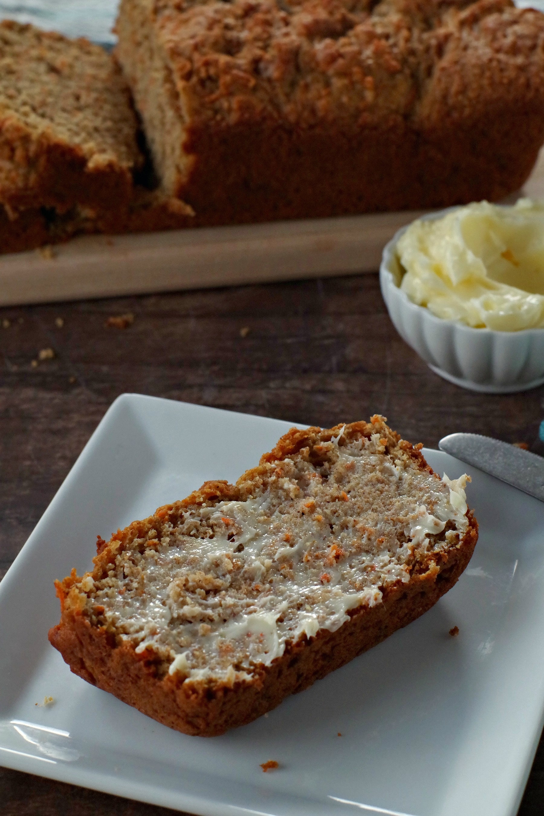 healthy carrot loaf slice with butter on a white plate with white dish of butter in the background. There is also a narrow wooden bread board in the background with the remainder of the carrot loaf on it (partially sliced)
