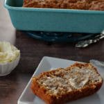 healthy carrot loaf slice with butter on a white plate with white dish of butter in the background. There is also a blue loaf pan in the background with the remainder of carrot loaf in it, as well as a silver knife beside the loaf pan.