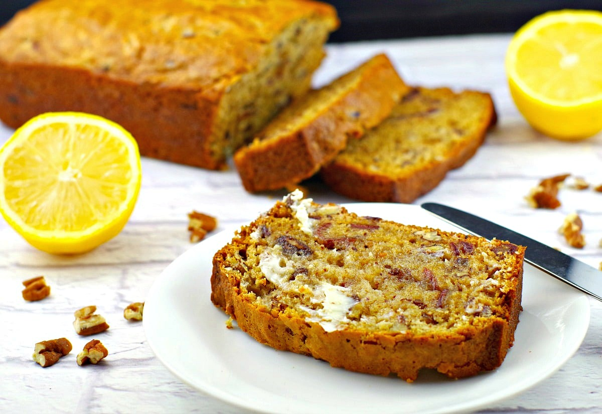a slice of date loaf on a white plate with whole date loaf in the background (partially sliced) and sliced lemons on the side