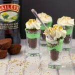 Irish cream dessert shots with a bottle of irish cream in the background, on a white faux surface