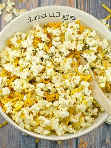 Savory popcorn in a white bowl, with the words 'indulge' on it, with a wood in it