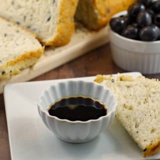 Loaf of Bread Machine Onion and Olive Bread, container of black olives and oil and vinegar in a dish with piece of bread for dipping