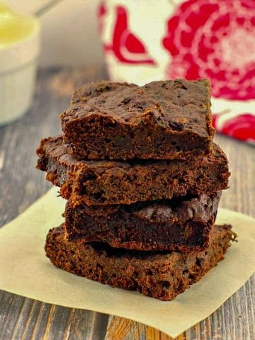 4 brownies with spinach stacked on a piece of parchment paper with applesauce and a red and white tea towel in the background
