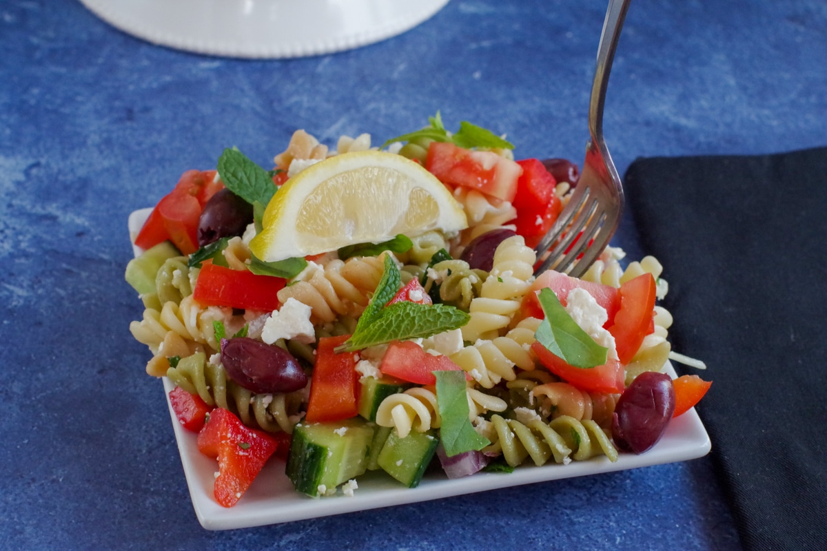 Greek pasta salad on white plate on blue surface