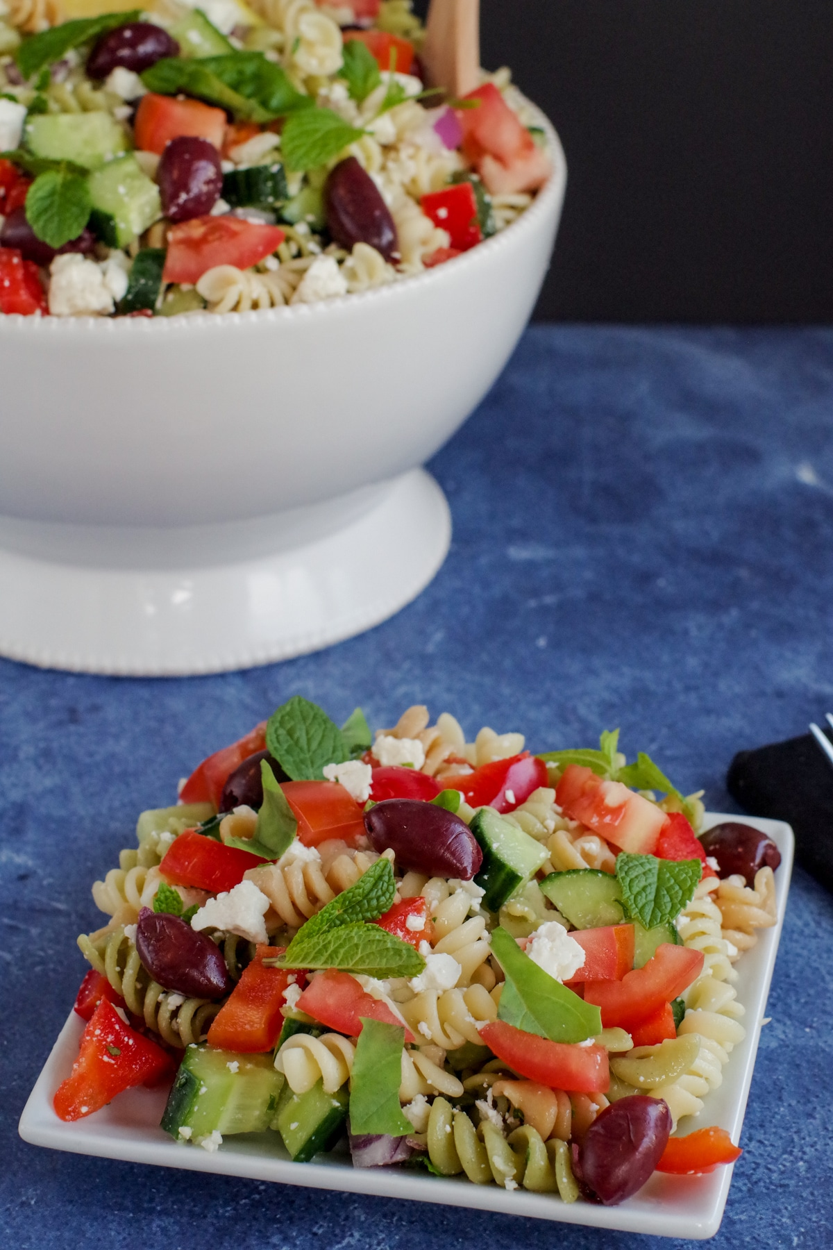Greek pasta salad on white plate with white bowl of Greek pasta salad in background, on blue surface