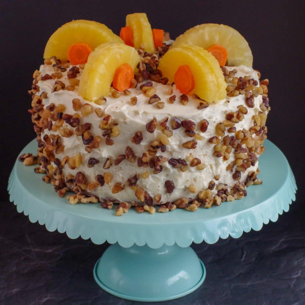 whole carrot cake decorated with pineapple and carrots on a aqua cake stand