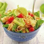Thai Chicken Noodle Salad in a blue bowl on white surface with green napkin in background