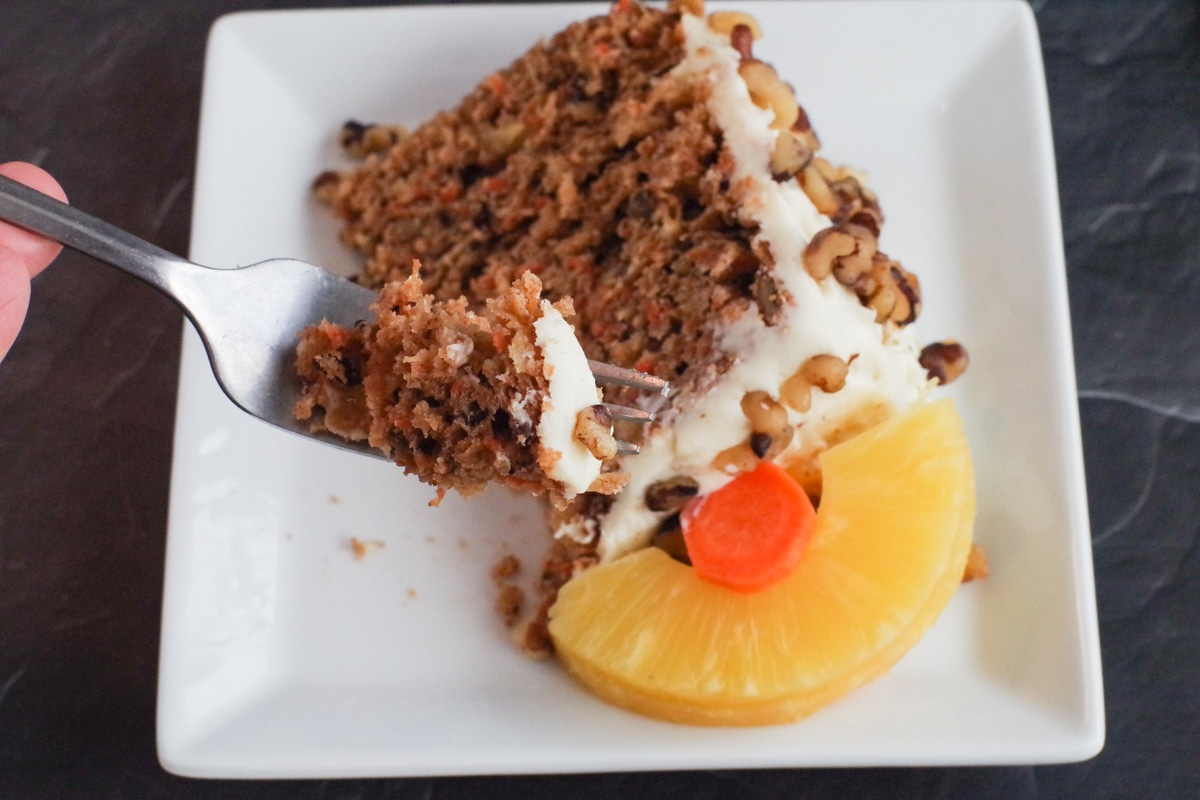 slice of healthy and light carrot cake on a plate with fork lifting bite out of it