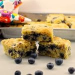 3 pieces of blueberry cornbread stacked on a counter with a pan of blueberry cornbread in background