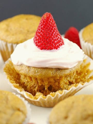 Pancake cupcake with Greek yogurt and strawberry topping, on loosened muffin liner wrapper, with other cupcake pancakes around it