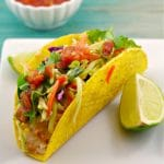 healthy fish taco on a white plate with a wedge of lemon