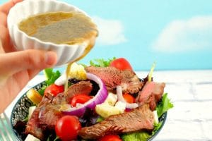 Moxie's Copycat Grilled Steak Salad with Clamato dressing being poured on top