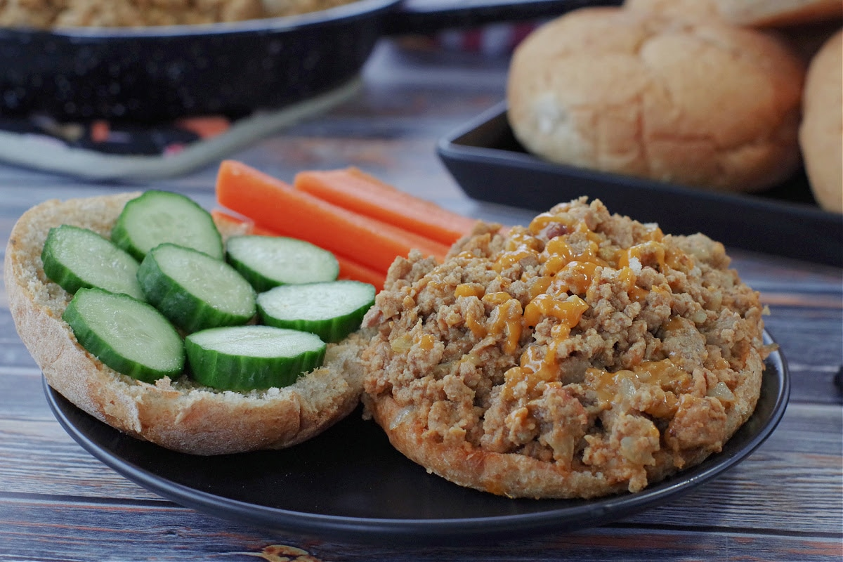 photo of weight watchers turkey sloppy joes on a black plate with carrots and cucumbers