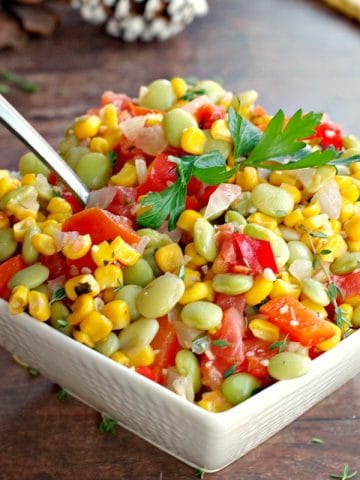 corn succotash in a white bowl with pine cones in the background