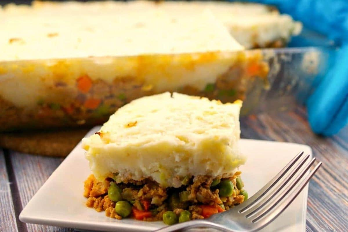 ground turkey shepherd's pie on a white plate with a fork and glass pan of ground turkey shepherd's pie in the background
