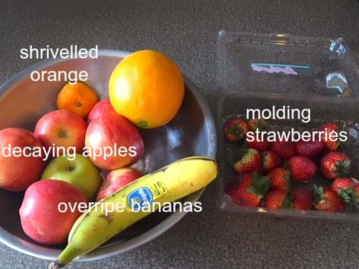 overripe fruit in a bowl and spoiling strawberries in plastic container on counter