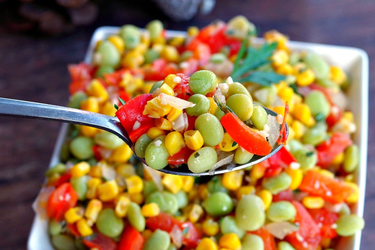 corn succotash being held up on a silver spoon with a dish of succotash below