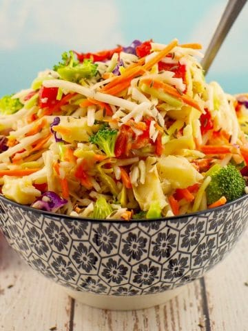 Healthy coleslaw in a black and white patterned bowl with a spoon sticking out of the coleslaw