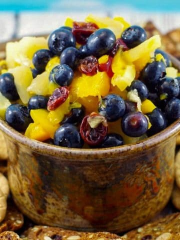 pineapple peach fruit salsa in a brown dip bowl on platter with cookies around it
