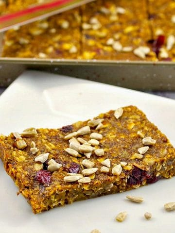 Healthy Fruit and Oat Bars on white plate with pan of more in the background