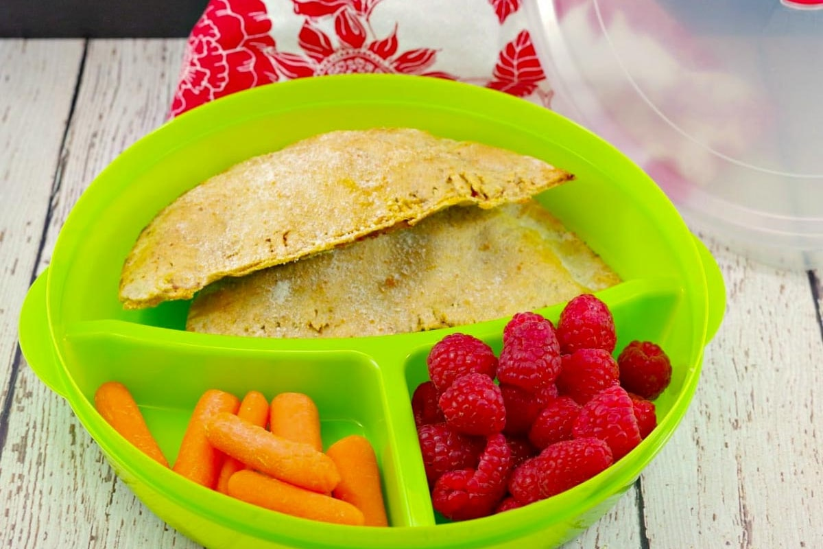 2 healthy homemade pizza pops in a 3 section green divided lunch container with raspberries in one section and baby carrots in the other
