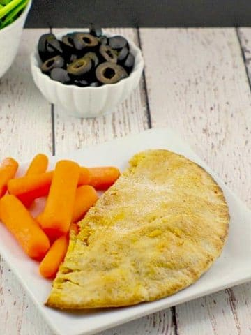 a healthy pizza pocket on a white plate with baby carrots and a dish of olives and spinach in the background