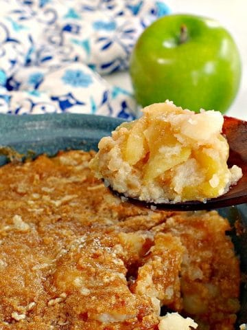 turnip and apple casserole (weight watchers friendly in a blue casserole dish, being held up on a wooden spoon with a green apple and blue patterned oven mitt in the background