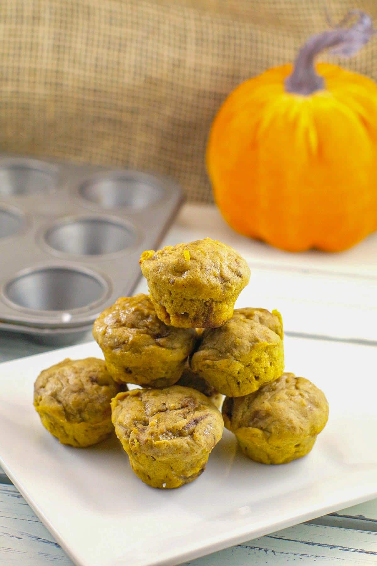 healthy pumpkin pie blondies stacked on a white plate with mini muffin tin and pumpkin prop in the background