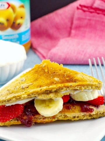 PB&J pancake sandwich on white plate with peanut butter, yogurt and red napkin in the background