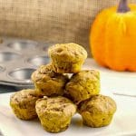 WW mini pumpkin muffins stacked on a white plate with mini muffin tin and pumpkin prop in the background
