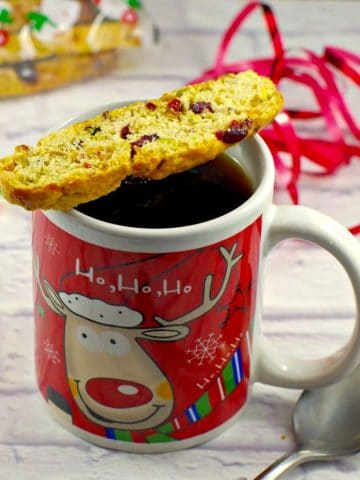 Christmas coffee mug with piece of biscotti on top, spoon on the side and ribbon in the background