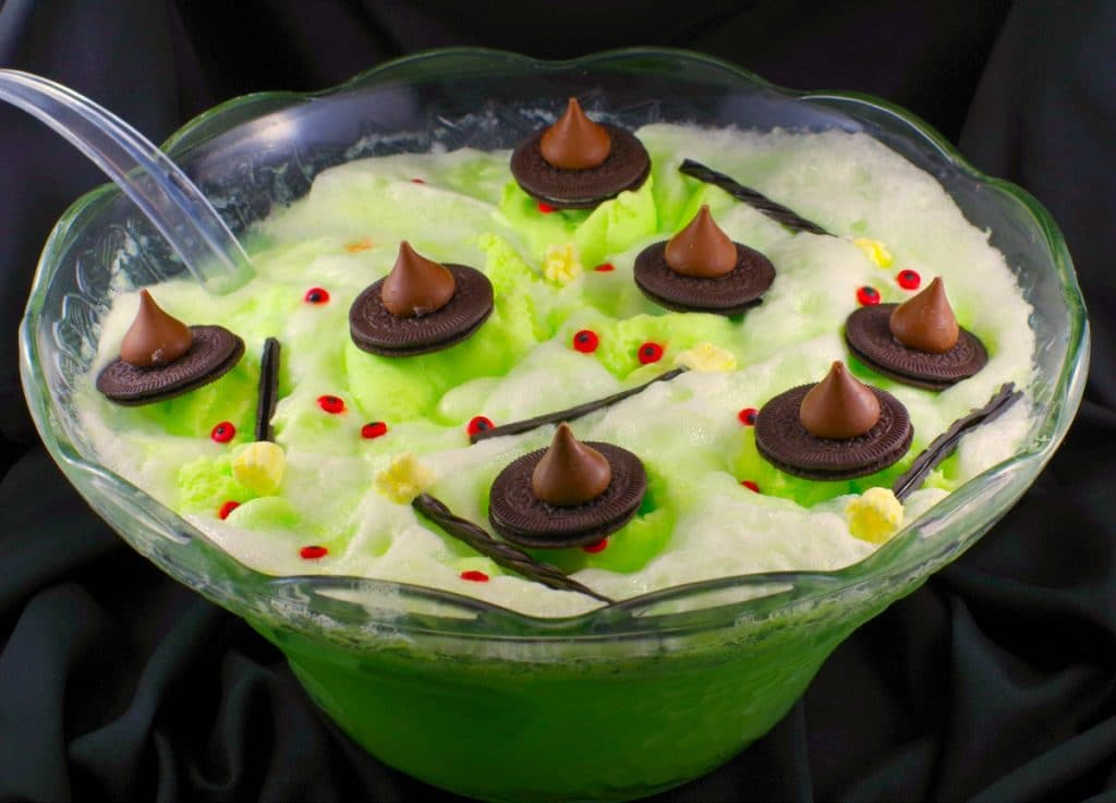 Melting witch green Halloween punch with chocolate hats, licorice marshmallow brooms and candy eyes