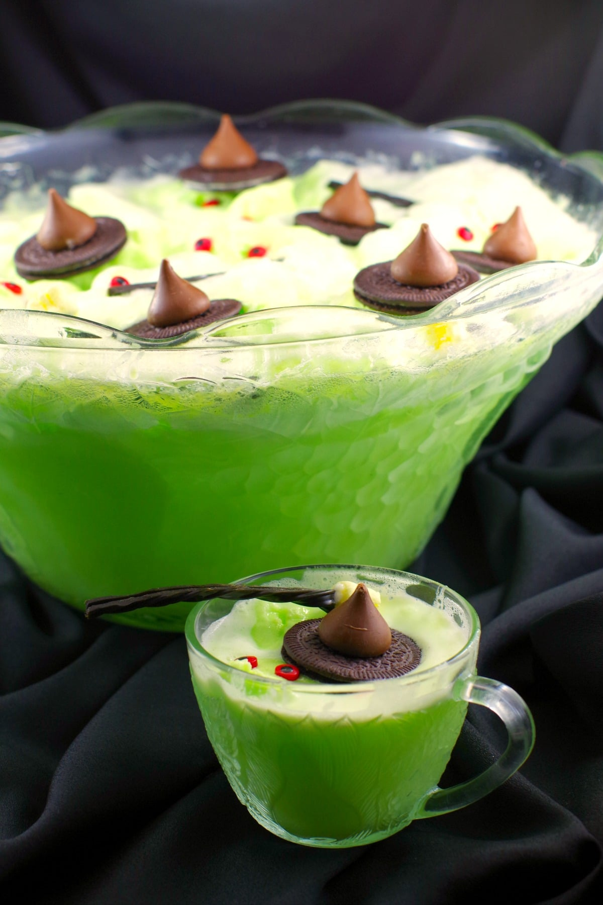 Melting witch Halloween punch for kids - green with cookie witch hats, licorice marshmallow brooms and candy eyes