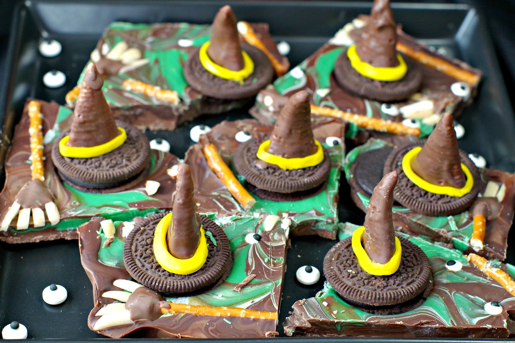 Melting Witch Halloween Chocolate Bark broken into pieces on black platter with extra candy eyes scattered on plate