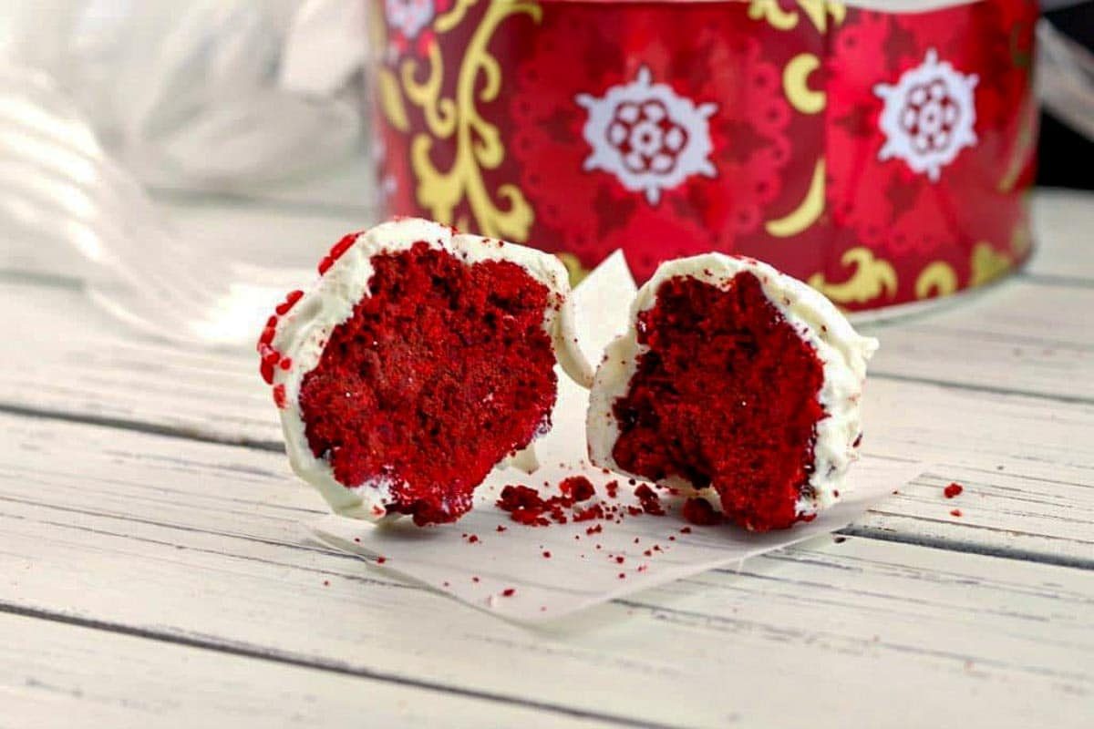 Red velvet brownie bite split in half, on a white wooden surface with Christmas cookie tin in background