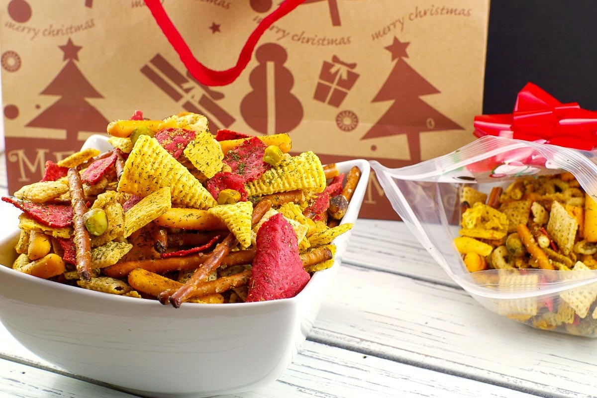 Christmas Chex Mix in a white bowl with a festive Christmas bag in the background