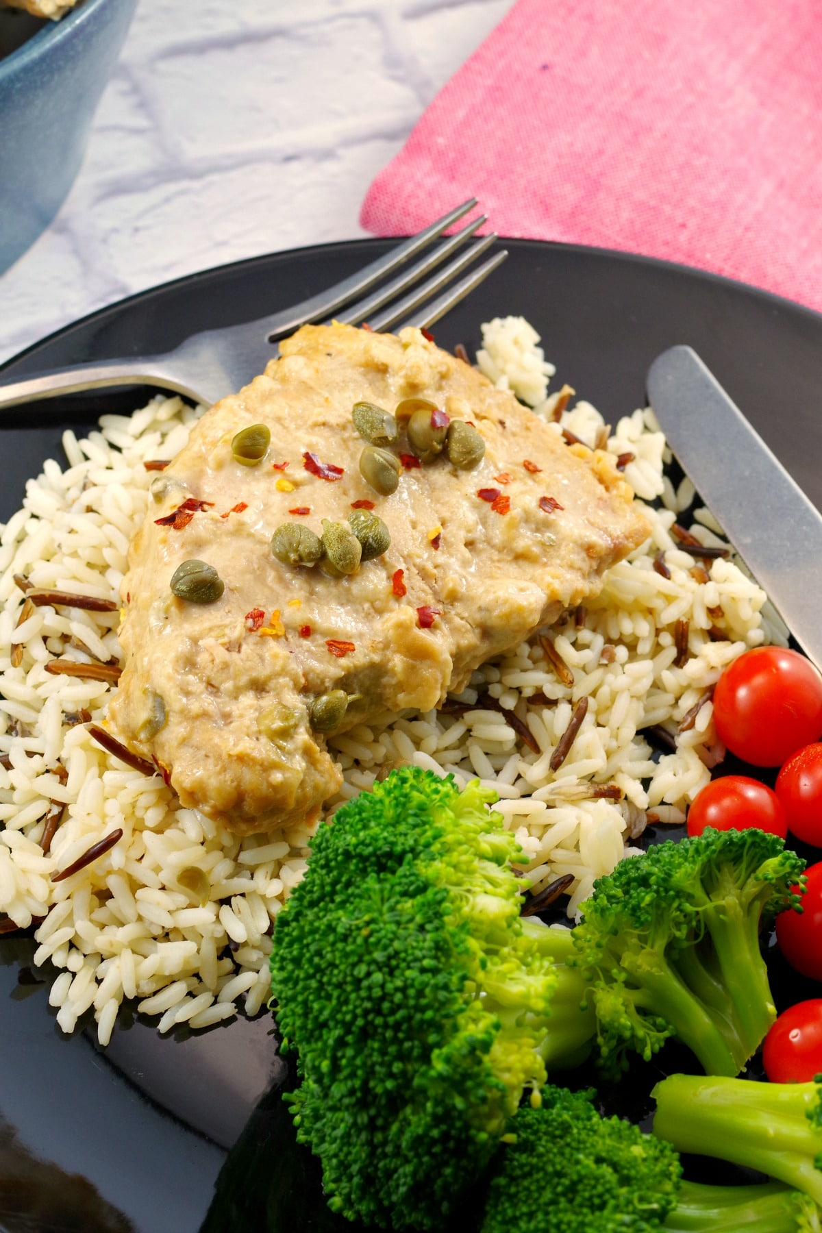 pork with creamy mustard caper sauce on a bed of rice, with salad and tomatoes on the side