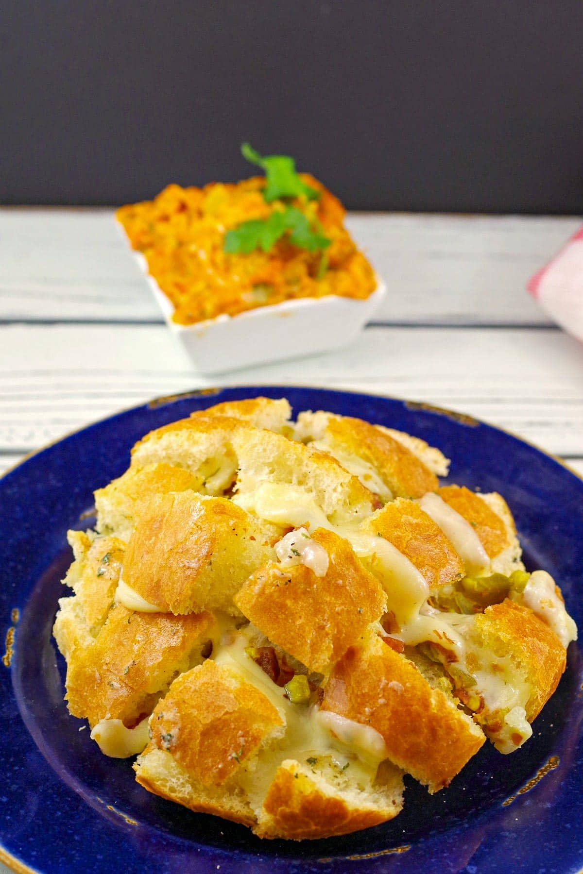 cheese and bacon pull apart bread on a blue plate with small bowl of dip in the background