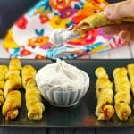 breakfast pigs in a blanket on black tray with dip in the middle and one being dipped into dip