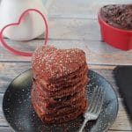 stack of 6 healthy red velvet pancakes on a black plate with a fork on the side, heart-shaped dish with chocolate cream cheese butter and white syrup container with heart shaped cookie cutter leaning against it, in the background