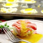 muffin tin eggs benedict on white plate with more muffin tin eggs benedict in muffin tin in background