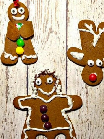 3 gingerbread cookies (a reindeer, dancing gingerbread girl and a gingerbread man) on a white faux wooden surface