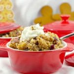 cranberry gingerbread rice pudding in a red bowl with gingerbread men and more red bowls in background