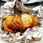 cooked, sliced, onion baked potato on foil