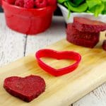 healthy jello hearts on cutting board with raspberries and spinach in the background