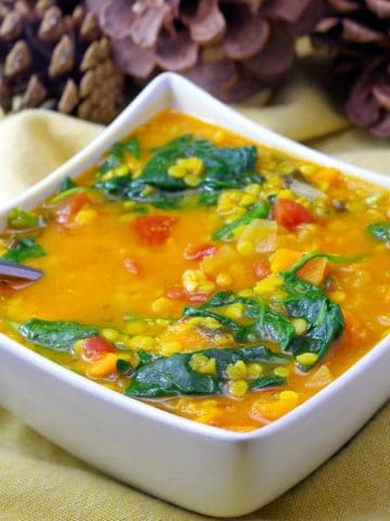 red lentil and spinach soup in a white bowl on yellow linens with pine ones in the background