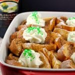 bailey's French Toast Casserole in white and orange dish with bottle of Bailey's Irish Cream in the background