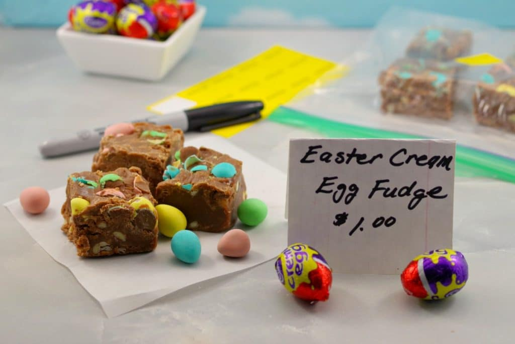 Easter Creme egg fudge on table at bake sale with sign and pen and sticker and more eggs in background