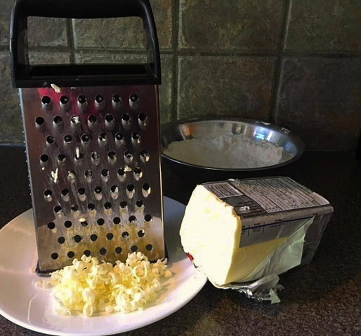butter being cut (for pastry) with a cheese grater